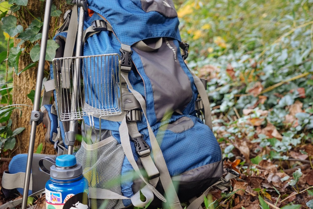 backpack and litter scoop in woods