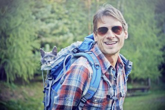 man hiking with cat in backpack