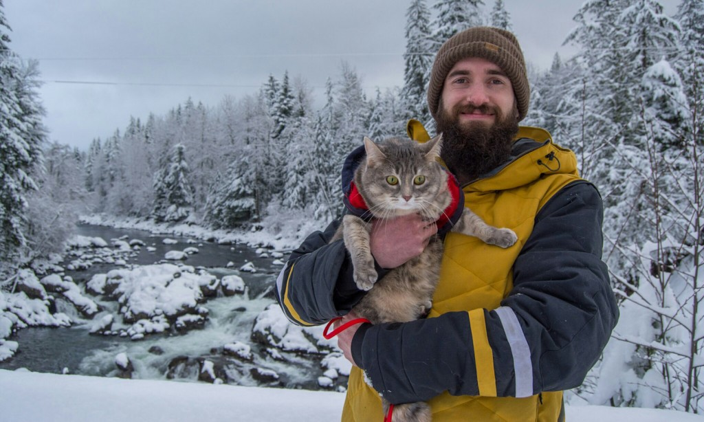 man holding cat in snow