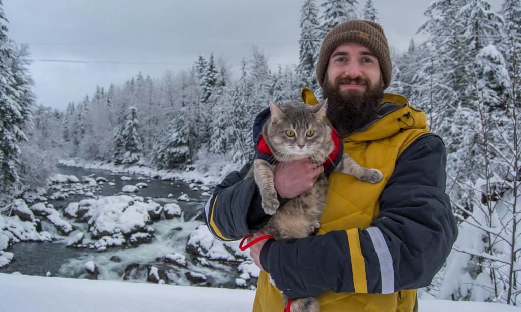 man holding cat in snow