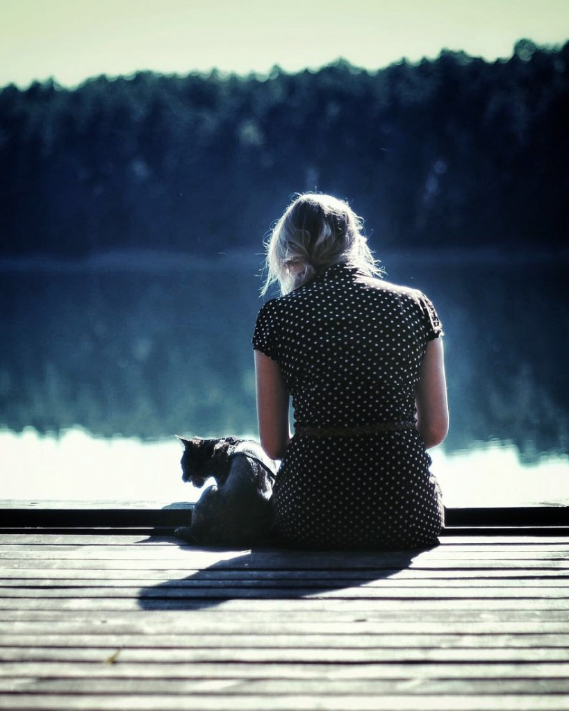 cat and owner sitting on dock