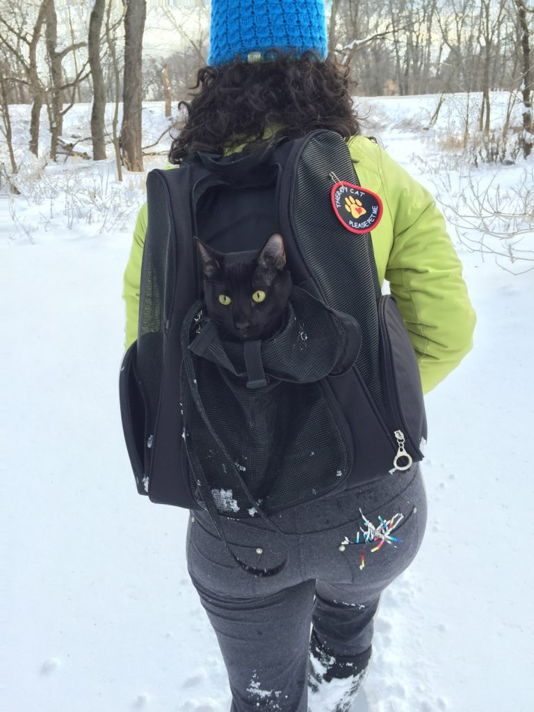 woman hiking with cat in backpack