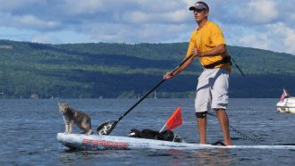 Dr. Ken paddle boarding with his cat Bug