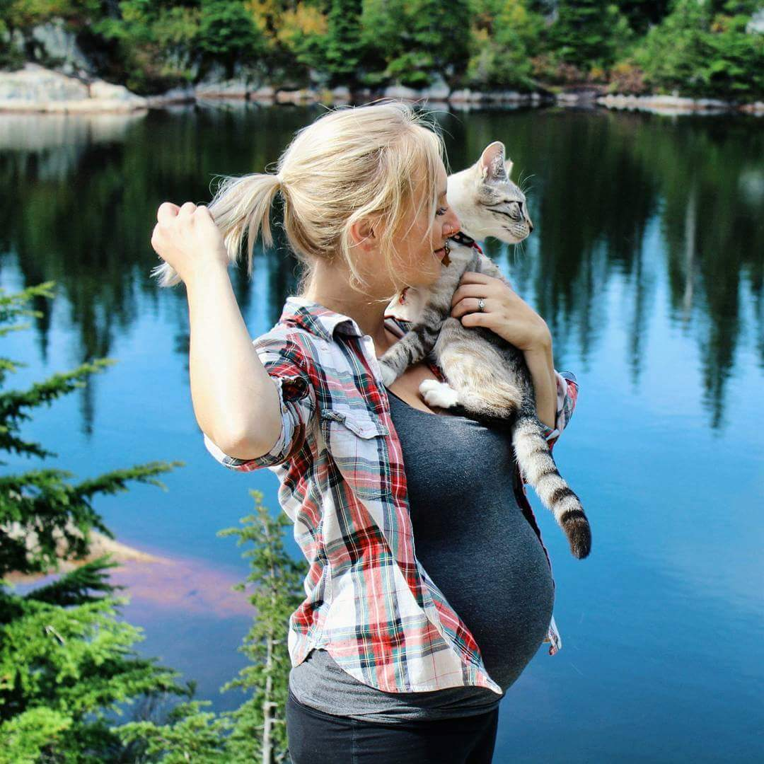 Pregnant Keshia looks out over the lake with her cat, Shasta