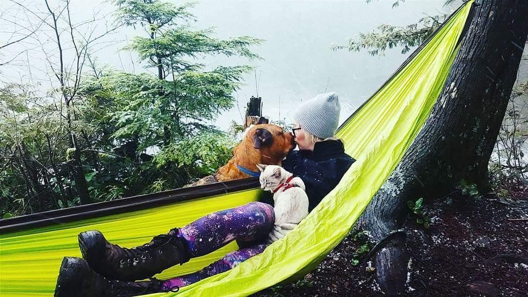 Keshia gives Winston a smooch while snuggling Shasta in a hammock