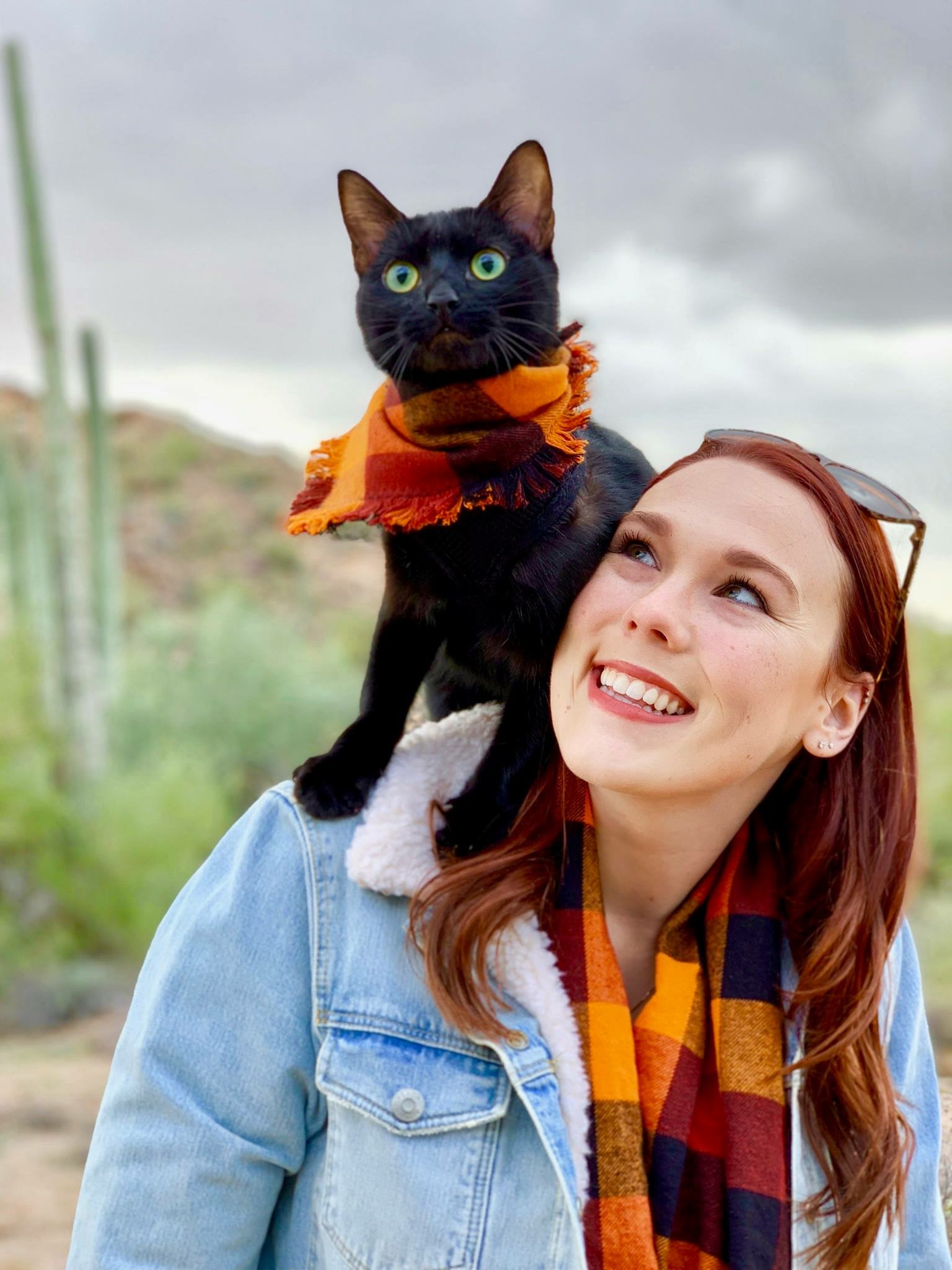 Cash rides on owner's shoulder while they wear matching scarves
